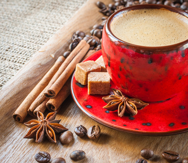 cup of coffee on wooden background decorated with spices